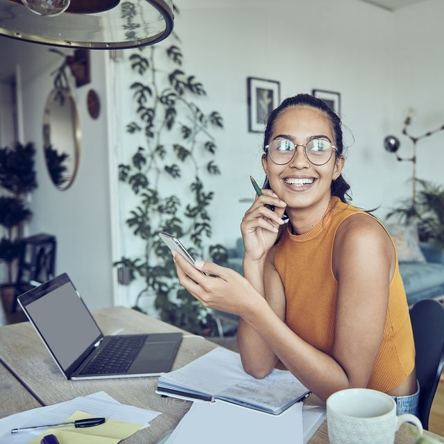 beautiful young woman working at home with laptop and documents