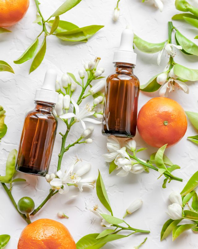 beauty concept of vitamin c serum in cosmetic bottles with dropper, tangerines, leaves and tangerine blossom on white background