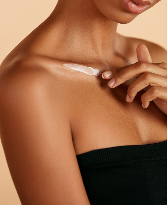 skin care closeup woman's body with cosmetic cream on skin beautiful black girl with moisturizing lotion on hydrated body skin at studio