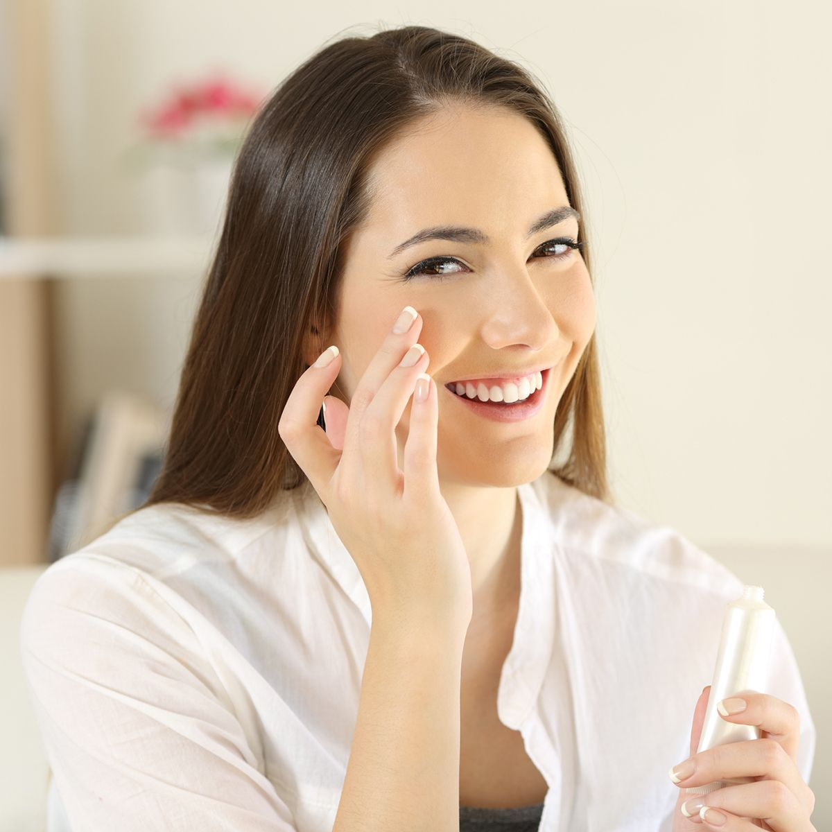 Woman applying moisturizer cream on the face