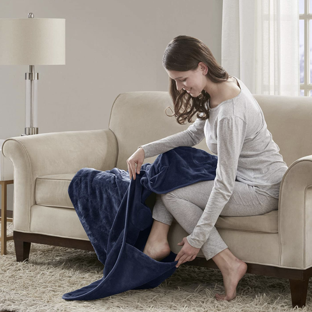 woman putting her feet in the foot pocket of a navy blanket