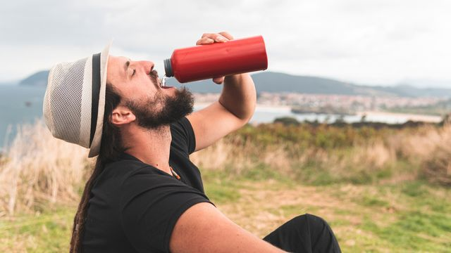 un hombre bebe agua de una cantimlpora