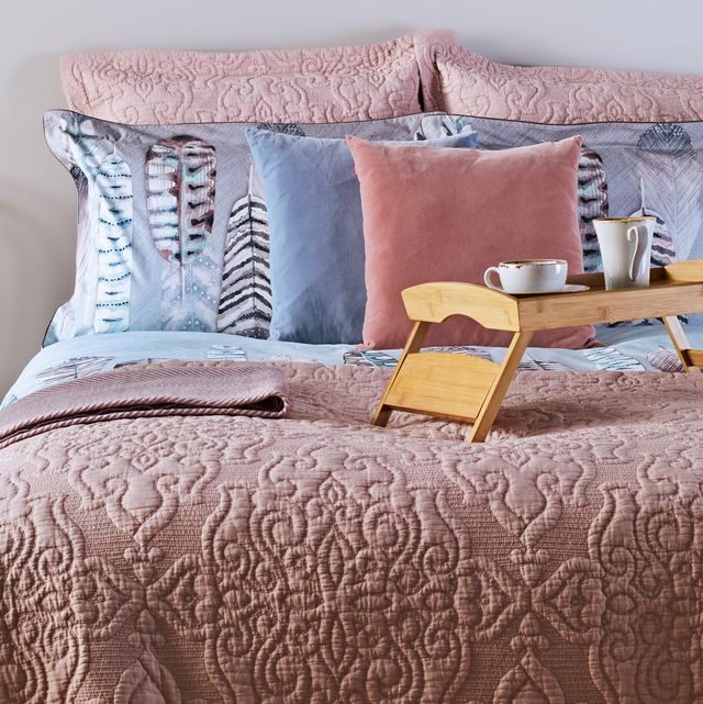 styled bed with pink quilt pillows and tray