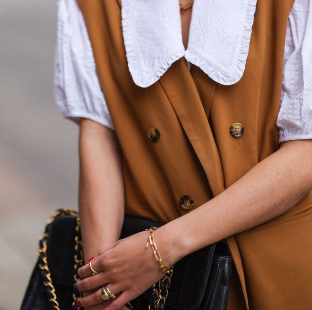 louisa theresa grass draagt een witte blouse met een bruin jasje zonder mouwen en een chanel tas en gouden sieraden