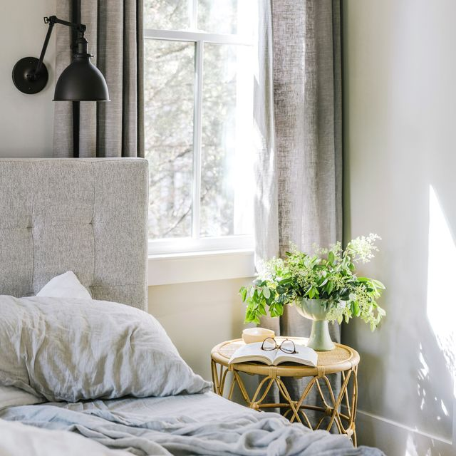 foraged spring flowers and branches on a table in a beautiful bedroom next to an unmade bed with linen sheets