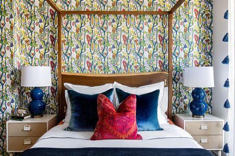 bedroom with canopy and colorful pillows