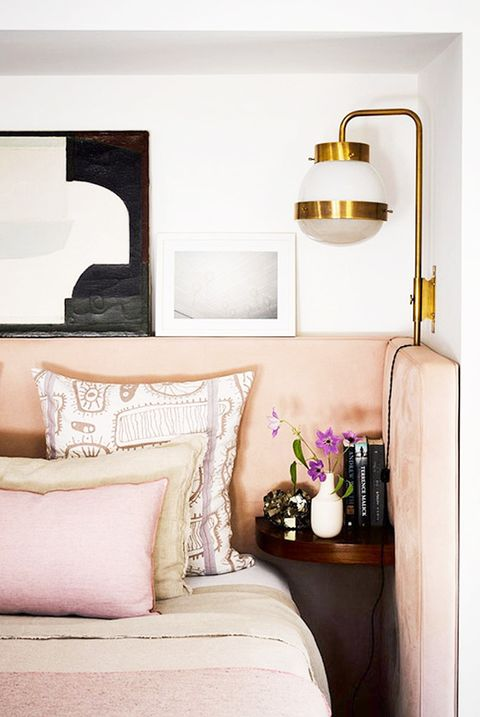 contemporary bedroom with gold sconce and pink frame