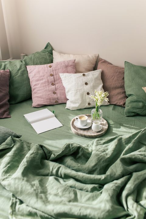 bedroom interior with bright green linen and pink cushions on bed