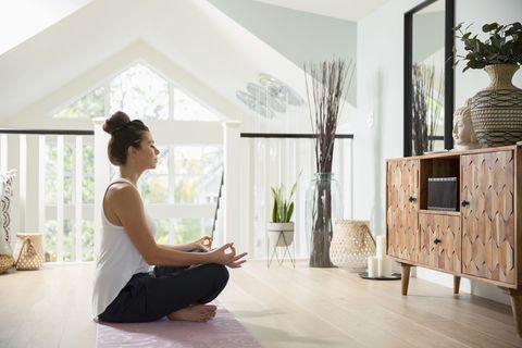 Vrouw mediteert thuis