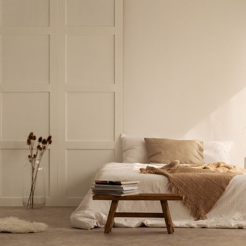 Beige blanket on the double bed in stylish wabi sabi bedroom of minimal style house, real photo with copy space on the empty wall