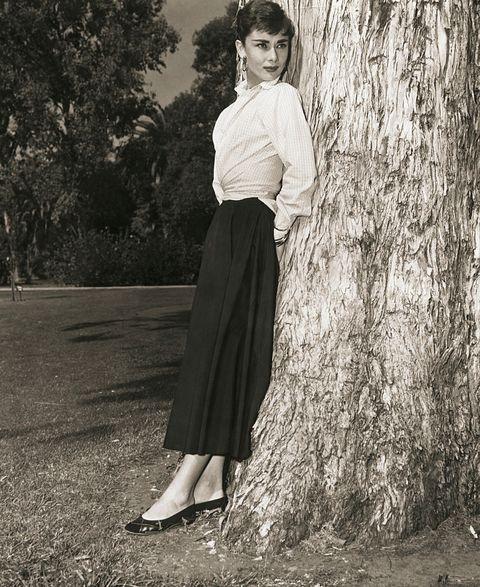 audrey hepburn leaning on tree trunk