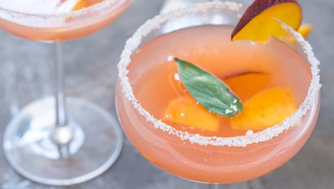 bellini cocktails with peach fruit and sage leaves