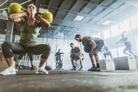 Below view of athletic people having cross fit training in a health club.