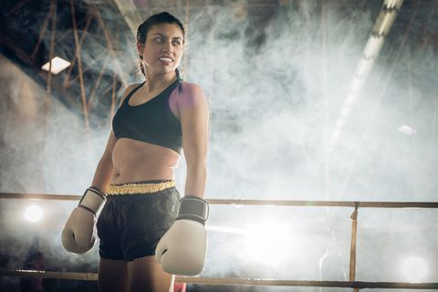 below view of happy female boxer standing in a ring