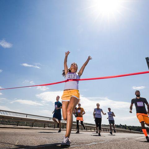 below view of successful marathon runner crossing the finish line