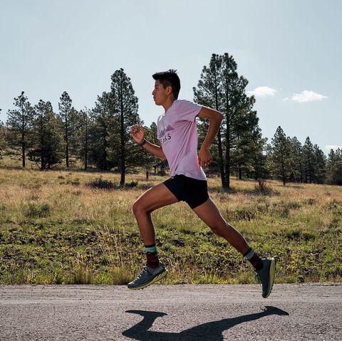 un hombre joven corre por una carretera en medio de un campo con bosques