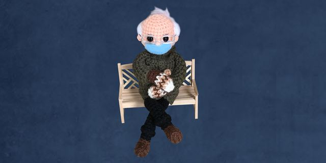 bernie sanders crochet doll sitting on a bench with brown mittens, face mask, and coat