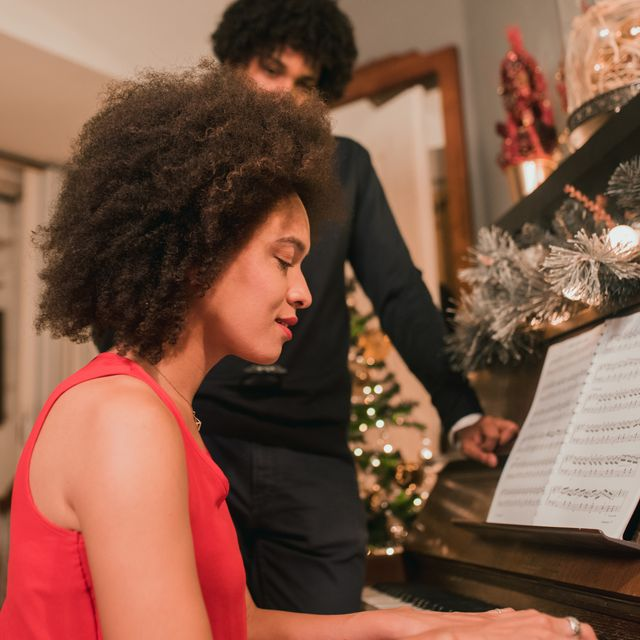 christian christmas songs   young woman playing piano during holidays