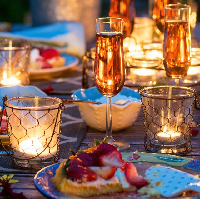 outdoor patio table set with citronella candles surrounded by dessert wine and strawberry tarts