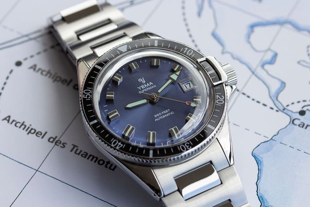 silver yema watch with blue dial resting against map