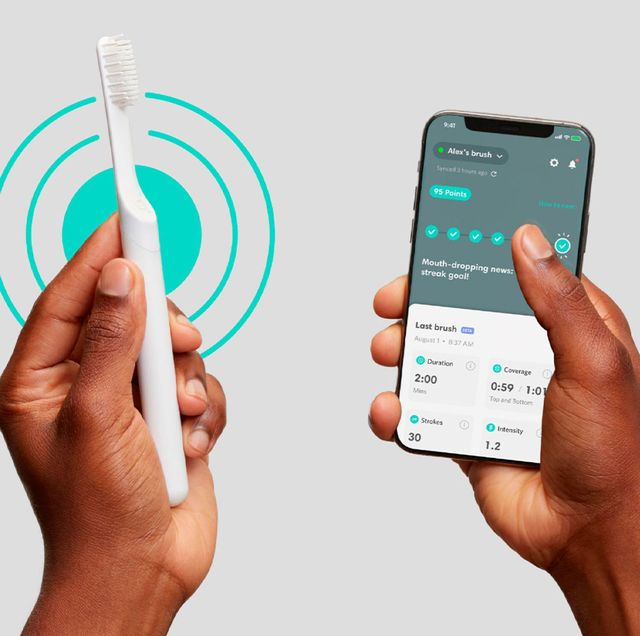 two hands holding a bluetooth quip toothbrush and phone
