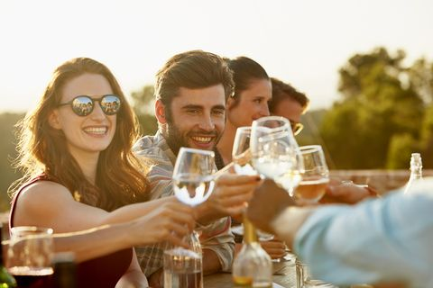 group of friends toasting and laughing while having dinner outside