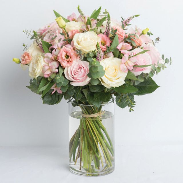 bouquet of white and pink flowers and clear vase bouquet of red, pink, white, and peach flowers in burlap sack tied with ribbon