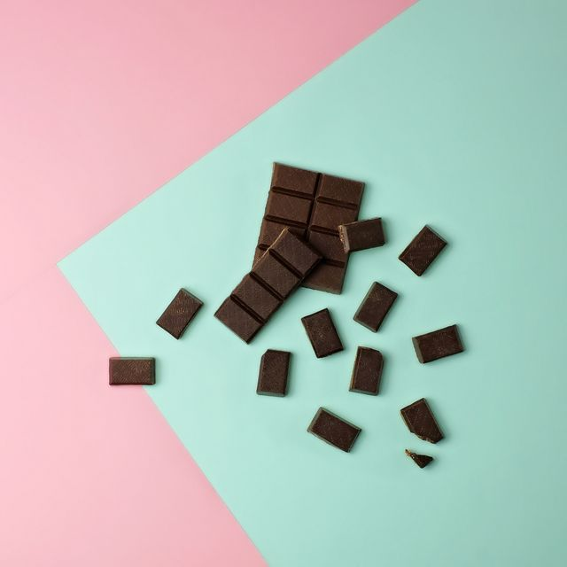 dark chocolate bar pieces on a pink and mint green color blocked background