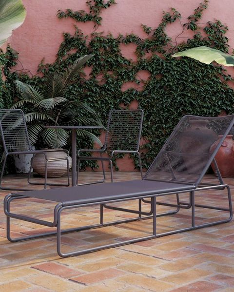 grey metal and wicker sun lounger in brick garden with pink wall and plants against the wall