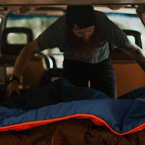 man setting up ignik heated blanket in car