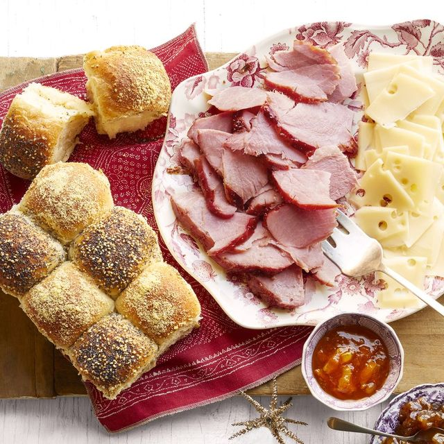 sliced ham and sliced cheese on platter with rolls