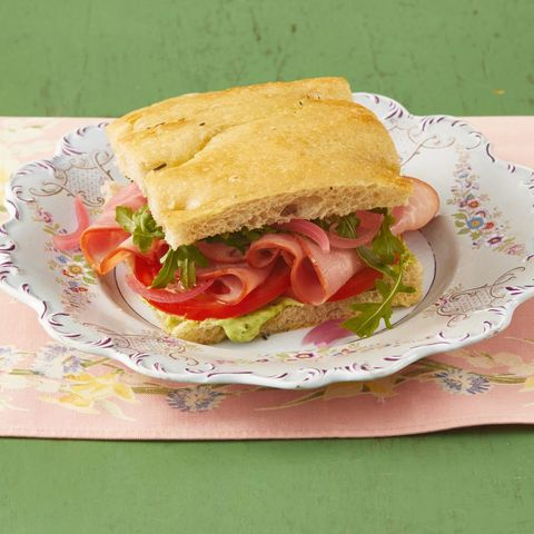 ham sandwich with arugula and pesto mayo on floral plate and pink linen