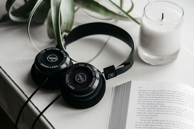 grado black headphones laying against white counter with a candle and book