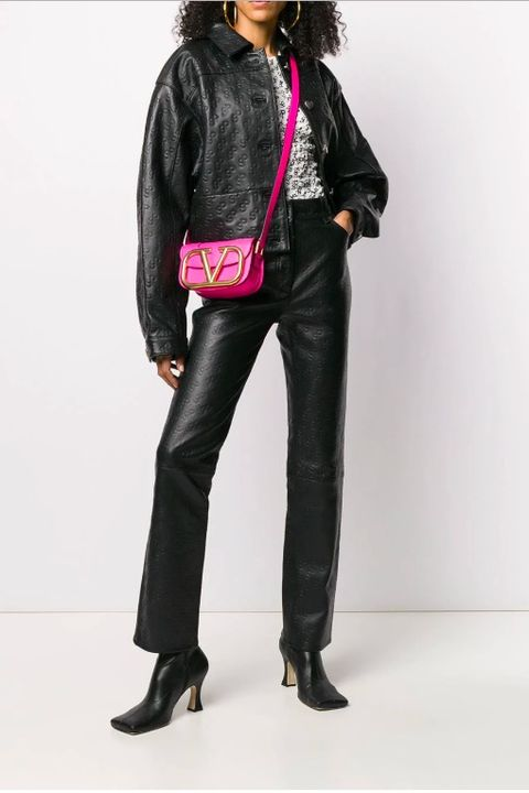 Amodel wears a black cropped leather jacket with silver heart buttons. The jacket has a collar and is emblazoned with the brand's SP logo. She is wearing matching leather trousers, a white top, and black boots.