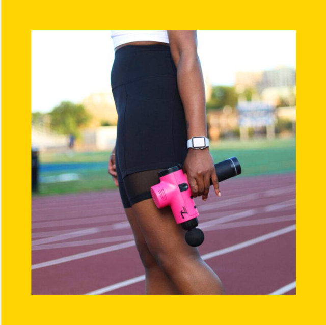hot pink massage gun being held by a woman on a track next to another smaller theragun