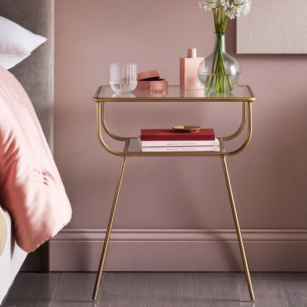 white side table, gold and clear side table next to bed