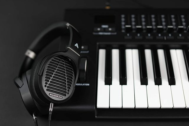 black audeze headphones laying on piano