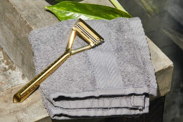 gold leaf razor laying against gray towel