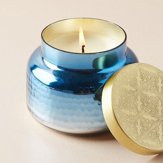 orange ombre candle and capri blue candle with gold lid leaning on it
