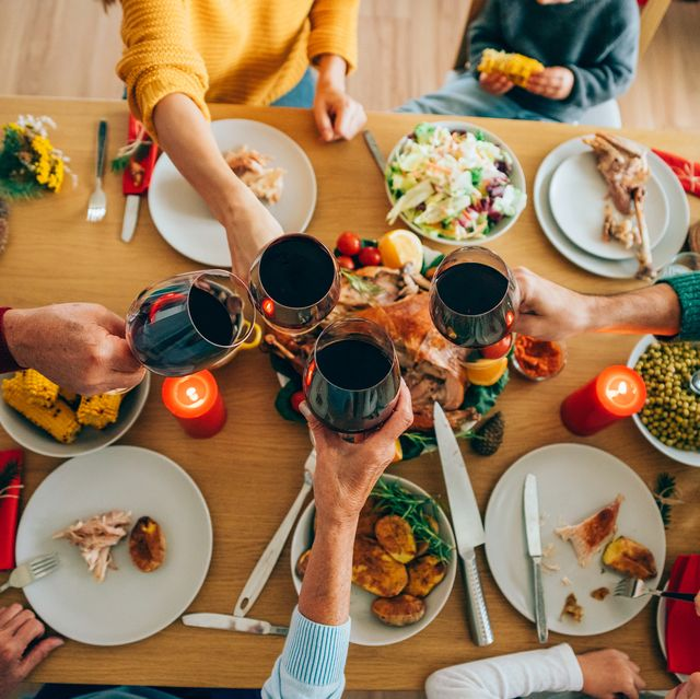group of unrecognizable people toasting with wine during thanksgiving or christmas dinner