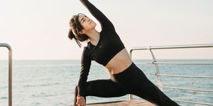 best yoga retreats: Young brunette woman in a black jumpsuit practicing yoga on the beach at sunrise. Concept of wellness and healthy lifestyle.