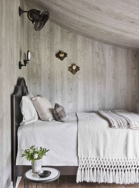 a bed in neutral linens tucked under the eaves and the wallcovering is faux bois