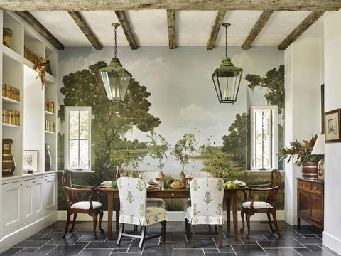 a landscape mural on one wall sets the scene for a wooden dining table and wood and upholstered chairs