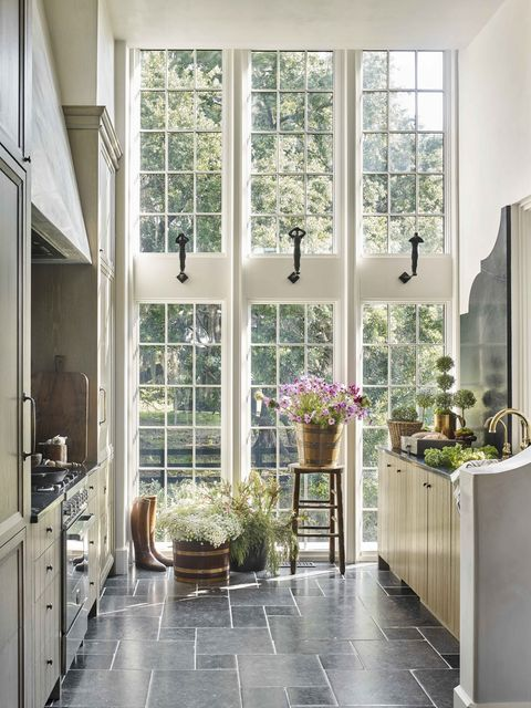 a wall of windows brings in natural light to a galley kitchen with stone countertops and floors