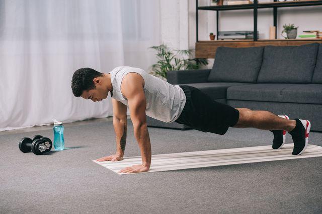 bi racial man doing push ups in sportswear on  fitness mat