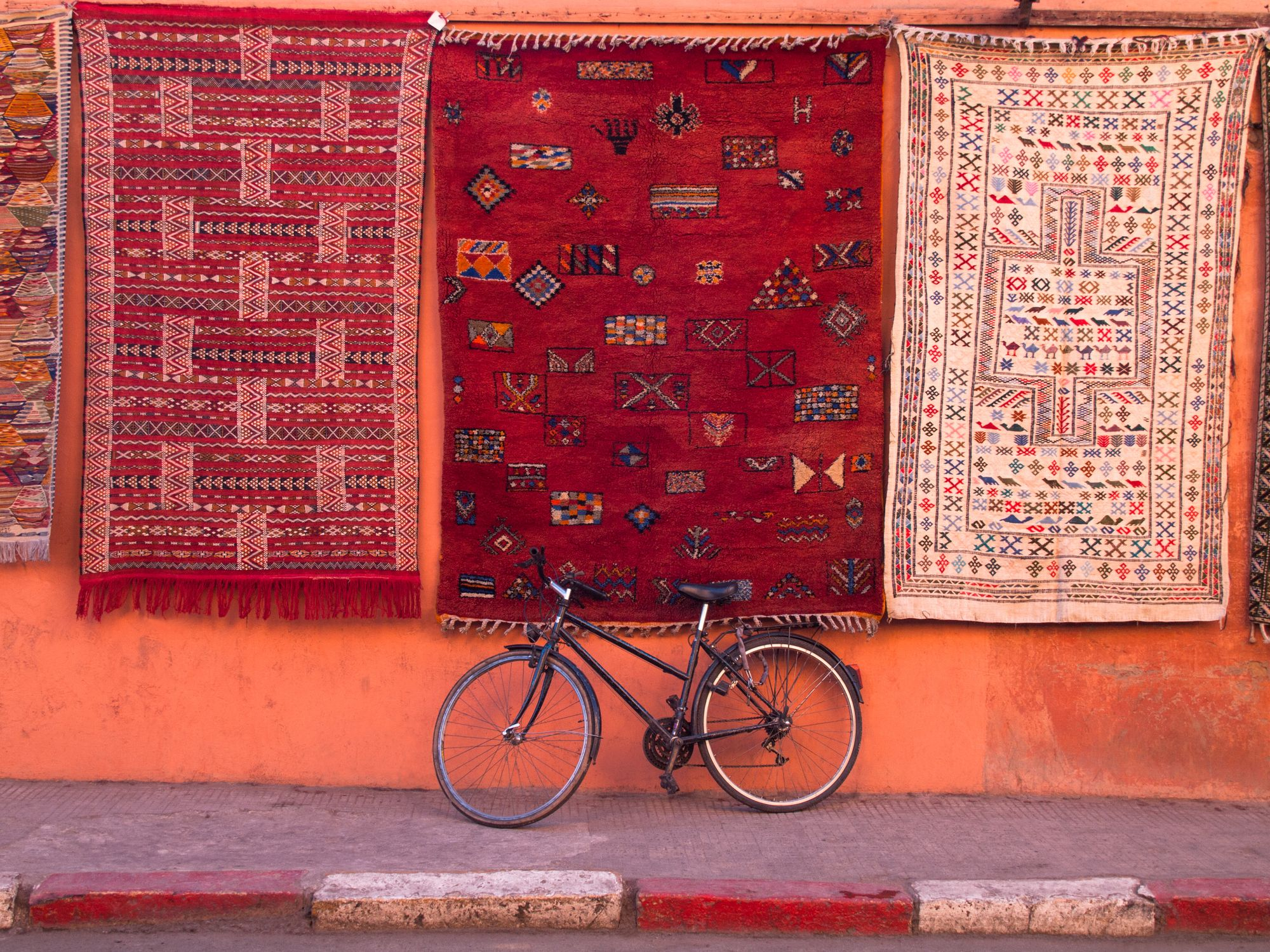 Bicycle parked at wall under hanging carpets with traditional patterns. Marrakesh, Morocco