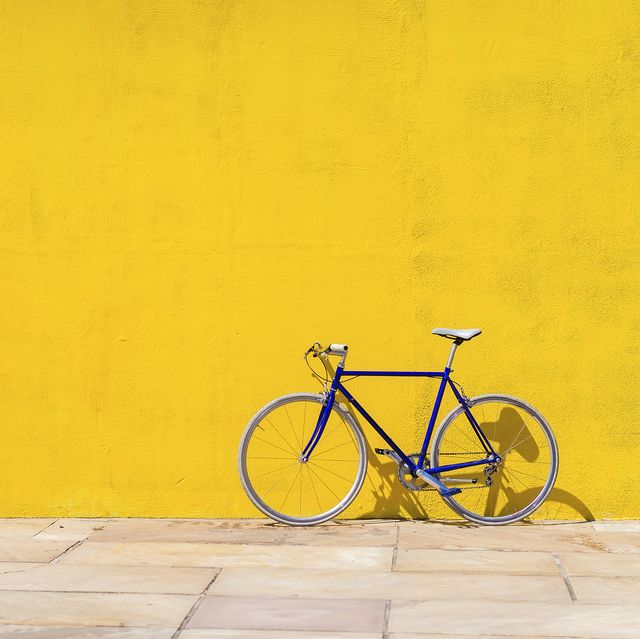 Bicycle parked on sidewalk by wall during sunny day