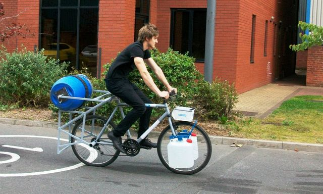 man on bike that operates as a laundry machine with a barrel attached to the back wheel