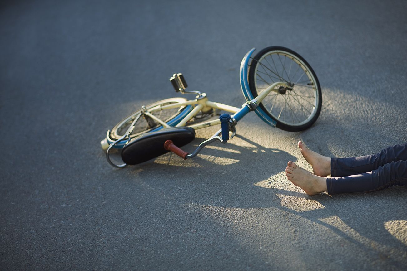 Child with bicycle fallen on street