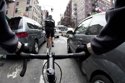cyclists in new york city bike lane between cars